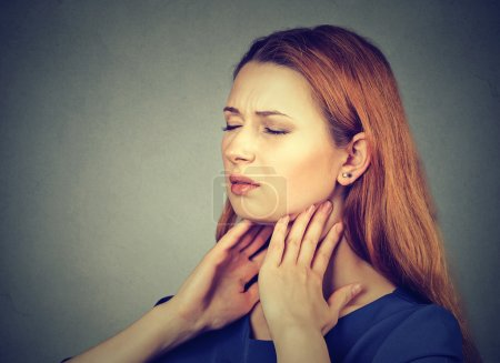 Sick young woman having pain in her throat