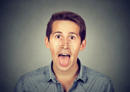 portrait of young man sticking out his tongue