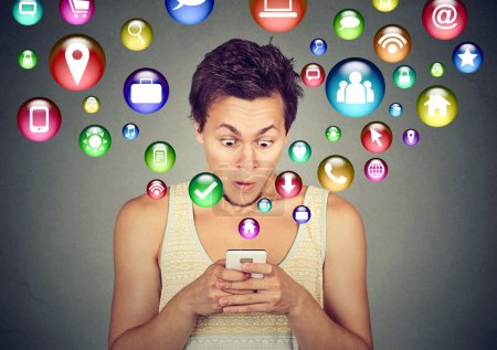 Shocked man using smartphone application icons flying out of cellphone