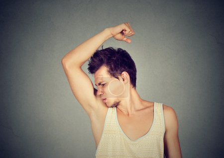 Photo for Closeup portrait of young man, smelling, sniffing his armpit, something stinks, very bad, foul odor situation, isolated on gray wall background. Negative emotion, facial expression, feelin - Royalty Free Image