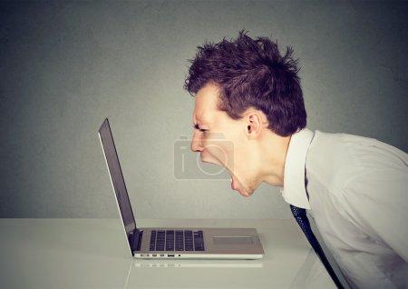 Photo pour Homme d'affaires en colère travaillant sur ordinateur portable - image libre de droit