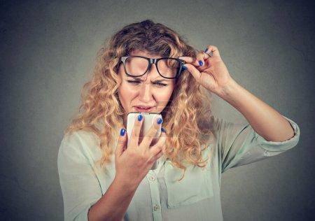 Photo pour Closeup portrait tête jeune femme avec des lunettes distinctement téléphone portable a des problèmes de vision. Mauvais texto. Perception d'expression faciale de l'émotion humaine négative. Technologie de confusion - image libre de droit