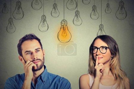 Photo pour Compétences cognitives concept de capacité, mâle vs femelle. Jeune homme et femme regardant ampoule lumineuse isolé sur fond de mur gris - image libre de droit