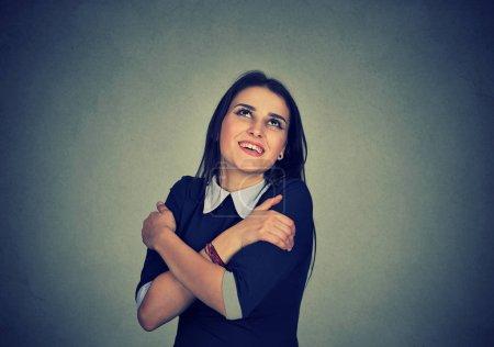 smiling woman holding hugging herself
