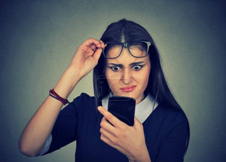 confused woman with glasses having trouble seeing cell phone