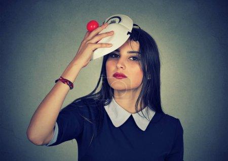 Photo pour Jeune femme enlevant un masque. Se faire passer pour quelqu'un d'autre - image libre de droit