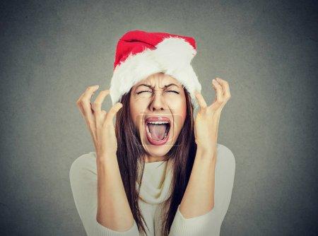 worried stressed overwhelmed woman wearing santa claus hat screaming