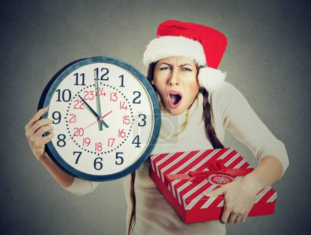 stressed in a hurry woman wearing santa claus hat holding clock gift box