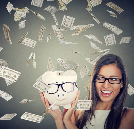 Photo for Save money on glasses eyewear. Portrait of happy girl excited over savings under money rain falling down dollar bills. Piggybank and woman wearing glasses isolated on gray background. - Royalty Free Image