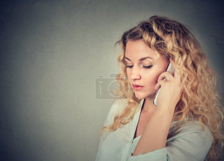 Photo for Young sad woman talking on mobile phone - Royalty Free Image