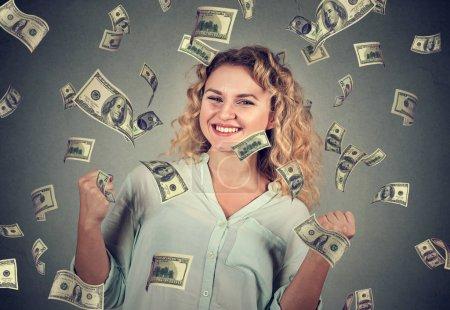 woman exults pumping fists celebrates success under money rain