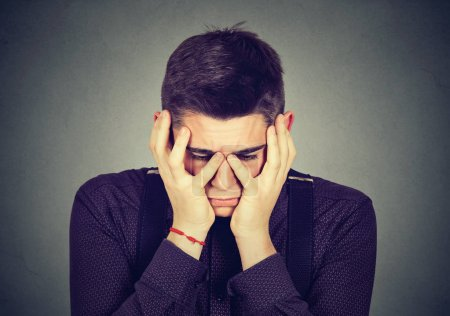 Photo for Desperate sad young man crying in his hands - Royalty Free Image