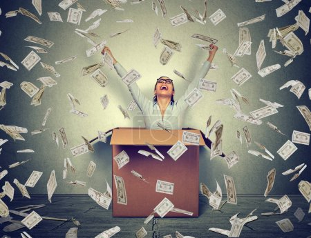 Successful woman coming out from a box under money rain