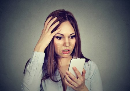 Upset woman looking at cellphone worried with message she received