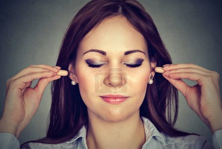 Noise control. Young woman with ear plugs