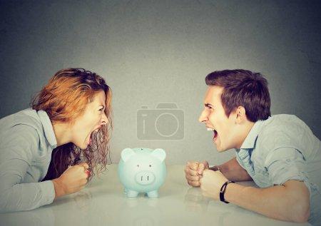 Photo pour Finances dans la notion de divorce. Femme et le mari ne peuvent pas faire règlement crier tirelire entre-deux assis à table, regardant les uns les autres avec la haine - image libre de droit