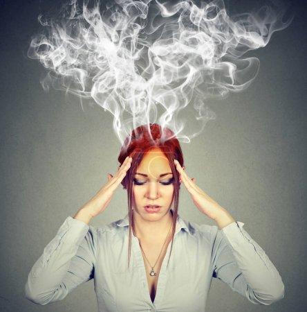 Foto de Piensa mujer muy intensamente, tener dolor de cabeza aislado sobre fondo de pared gris - Imagen libre de derechos