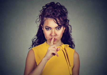 Secretive woman with finger on lips asking shh, quiet