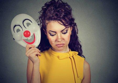 Mujer triste quitándose la máscara de payaso expresando alegría