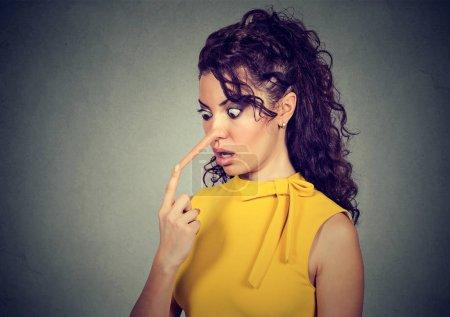 Photo pour Femme choquée avec le nez long isolé sur fond de mur gris. Concept menteur. Expressions du visage humain, émotions, sentiments - image libre de droit
