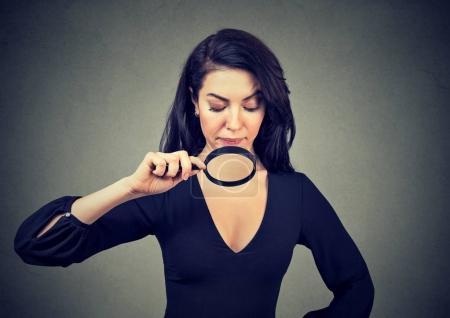 Photo pour Jeune femme en regardant ses seins à loupe - image libre de droit