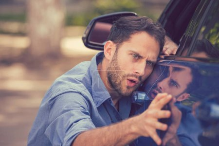 Worried funny looking man obsessing about cleanliness of his new car