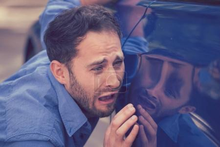 Aufgebrachter Mann sieht Kratzer und Dellen an seinem Auto im Freien