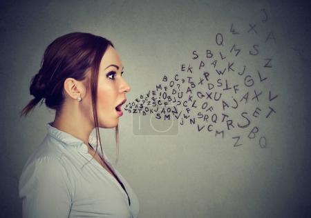 Photo pour Femme parlant avec des lettres de l'alphabet sortant de sa bouche . - image libre de droit