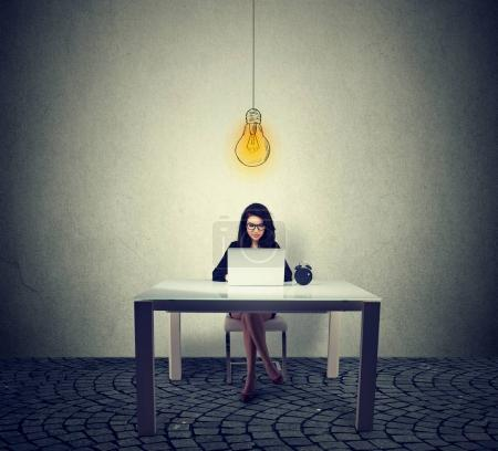 Photo for Young woman sitting at table working on laptop with bright light bulb above head - Royalty Free Image