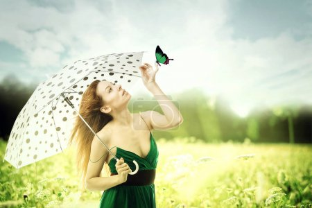 woman with umbrella walking though a park playing with a butterfly