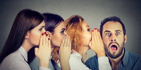 Photo pour Trois jeunes femmes chuchoter chaque homme étonné et d'autre à la choqué à l'oreille. Concept de communication de bouche à oreille. Réaction d'expression de visage émotion humaine - image libre de droit