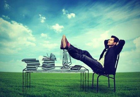 Photo for Happy business man relaxing at his desk outdoors in the middle of a green meadow, daydreaming - Royalty Free Image