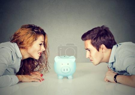 Photo for Finances in divorce concept. Wife and husband can not make settlement holding piggy bank sitting at table looking at each other with hatred - Royalty Free Image