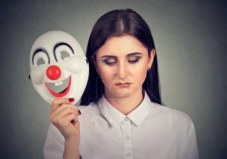 mujer triste quitándose la máscara de payaso expresando felicidad