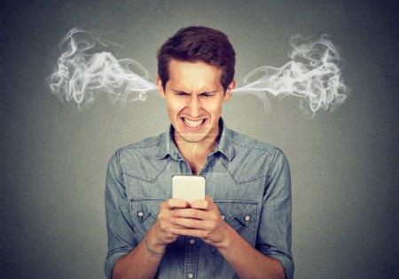 Photo pour Homme en colère frustré lisant un message texte sur son smartphone soufflant de la vapeur sortant des oreilles - image libre de droit