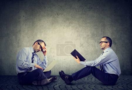 Photo pour Ordinateur contre livre. Deux hommes assis sur un sol l'un lisant un livre l'autre travaillant sur ordinateur portable - image libre de droit