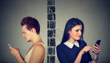 Pareja enojada molesta hombre y mujer separados por la pared degustación unos a otros en el teléfono móvil