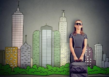 Photo pour Belle femme debout sur un fond de skyline de la ville et tenant une valise - image libre de droit