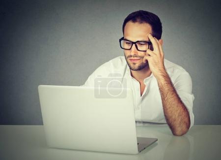 Photo pour Gros plan d'un homme d'affaires coûteux portant des lunettes assis au bureau travaillant sur son ordinateur portable - image libre de droit