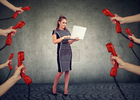 beautiful businesswoman with laptop surrounded by many hands with phone headsets