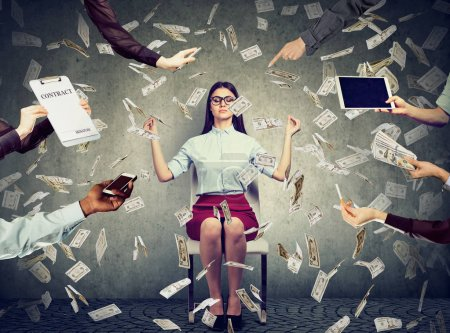 Photo for Young business woman is meditating to relieve stress of busy corporate life under money rain - Royalty Free Image