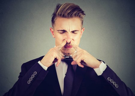 Photo for Man pinches nose with fingers looks with disgust something stinks bad smell isolated on gray background. - Royalty Free Image