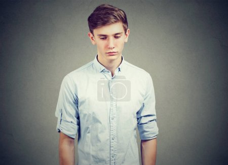 Photo for Closeup of a sad gloomy young man looking down - Royalty Free Image