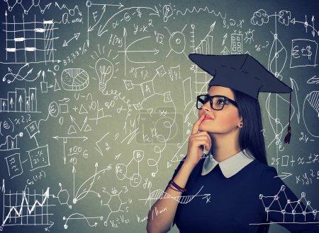 Photo pour Jeune femme intelligente en chapeau explorer les formules et la science regardant confiant et excité . - image libre de droit