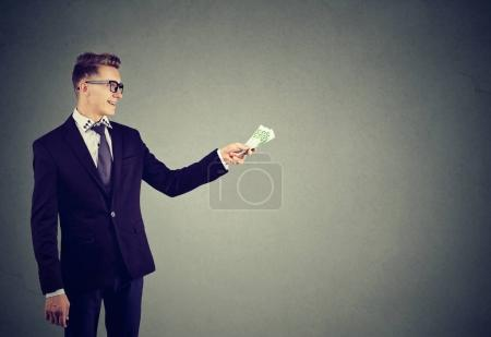 Young confident businessman giving money in credit...