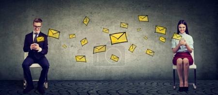 Photo pour Jeune homme et femme assis sur des chaises et bavarder avec des téléphones mobiles envoyer des SMS - image libre de droit