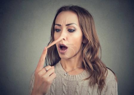 Photo pour Jeune femme occasionnelle toucher nez étendu de menteur regardant choqué . - image libre de droit