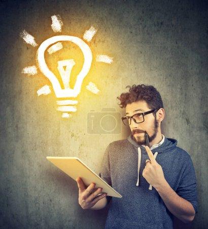 Photo pour Casual jeune étudiant en utilisant la tablette et la création d'une nouvelle idée en regardant vers le haut . - image libre de droit