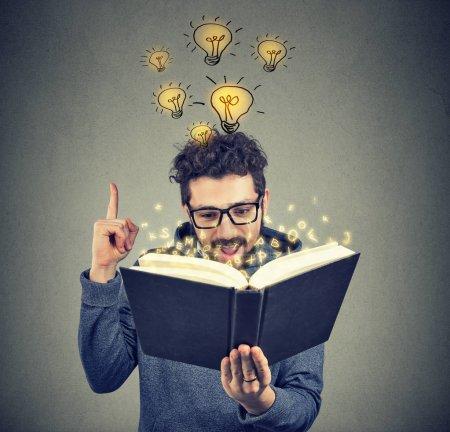 Photo pour Jeune homme ayant une idée brillante à venir à l'esprit tout en lisant le livre intelligent . - image libre de droit
