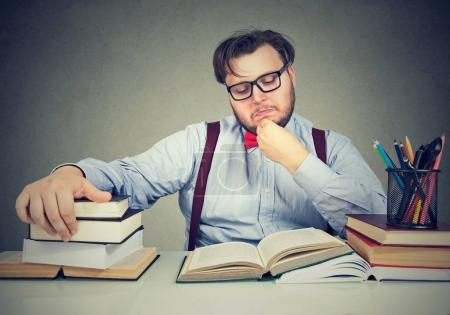 Young chunky man sitting at desk and reading books...